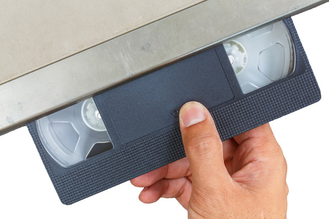 vhs tape being inserted in player