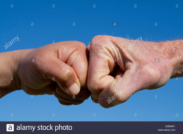 fists pound against each other on a blue background spain G3 E6 WY