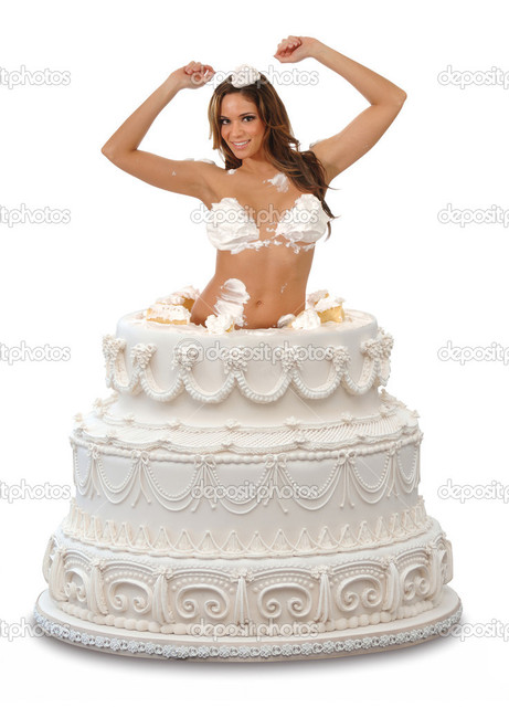 Attractive young woman popping out of a large cake against a white background