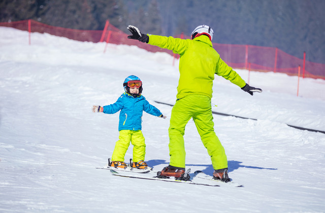 Lesson-at-skiing-school-instructor-teaching-little-skier-how-to-make-turns-young-boy-doing-exercise-