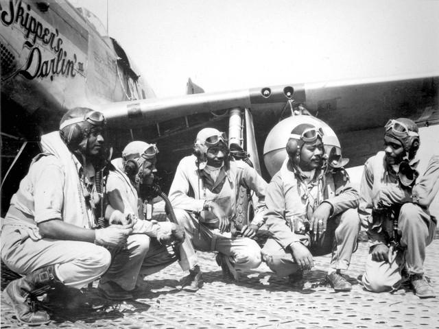 Un grupo de los Pilotos de Tuskegee del Grupo de Combate 332, desde la izquierda Tte Dempsey W. Morgan, Tte Carrol S. Woods, Tte Robert H. Nelson Jr., Capitán Andrew D. Turner y Tte Clarence D. Lester, arrodillados en frente de un Mustang P.51 durante la II Guerra Mundial