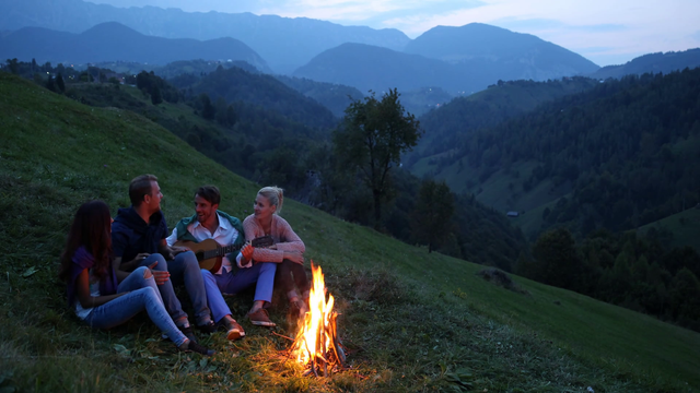 Young group of friends enjoying together playing guitar singing bonfire mountain hea53ibex thumbnail full15